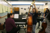 Lincoln High School student Storm Moreno, 15, a freshman, tunes his double bass with music teacher...
