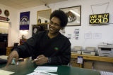 Marcus Sisk (CQ) , 23, of Denver works at the counter of Fast Cash Pawn and Jewelry. EDS visits...