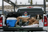 Terri Stangl (cq) tries to stay warm in the back of a pick-up truck, with her dog A.J. while...