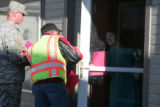 A National Guardsmen and CDOT worker hand out a informational flyer to a resident as they  canvas...