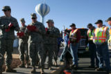 National Guardsmen and CDOT workers read an advisory they will leave with homeowners before they...