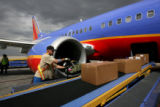 Southwest ramp worker, John Kachinko (cq), unloads a jet, Thursday afternoon, June 23, 2008, DIA,...