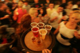 Lisa Helker (cq), 27, navigates her tray of drinks through the crowd at the rooftop bar of Sports...