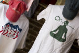 2 shirts hang on a small display that Tina Eyre(cq) keep in Julie Rubsam's garage on July 11,...