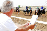 John Irlando, of Denver, looks over the card and surveys the horses as they walk toward the...