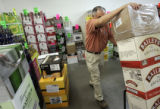 Wayne Archuleta (cq), of Pinnacle Distributing, moves liquor boxes and sets up displays at Lukas...