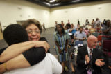 Carolyn Jones, founder of Challenges, Choices and Images charter school, hugs Ailey Pop, 18, after...
