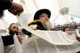 (PG03244) Rabbi Yisroel Engel (center) shows the Scroll of Esther to illustrate to reporters what...