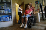 Janine Anderson (cq) tries on her new wheel chair as Carl McDill and his store assistant Nancy...