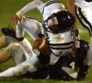 Lakewood, Colo., photo taken September 30, 2004- Columbine linebacker Mike Conklin (right) stops...