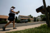 Michelle Wilson (cq) delivers mail in the area of 7800 block of S. Logan St. Friday afternoon, in...