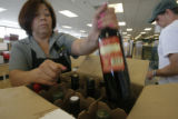 DM0237  Maria Rodriguez boxes up several bottles of wine for Brent Anderson on the first day of...