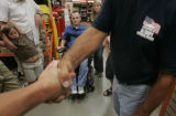 Homes for Our Troops volunteer Erik Freeman shakes Home Depot store manager Glenn Richardson after...