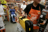 Home Depot manager Glenn Richardson loads power tools into a shopping cart as Matt Keil, back,...