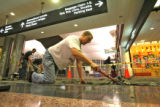 Paul Scrabeck (cq), foreground, scraps away old carpet glue, in the main terminal at DIA, Tuesday...