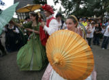 Members of the royal court hide behind their parasols from an angry queen at the Renaissance...