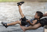 Jesus Perez (cq), 3, plays in the water with his grandfather Domingo Puc at Confluence Park in...