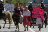 Protesters from the anti-war group CodePink march outside a hotel housing Republican vice...