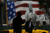 Pedestrians walk by a mural of Theodore Roosevelt in front of the Denver Convention Center on...