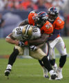 D.J. Williams and Marquand Manuel tackle Jeremy Shockey in the fourth quarter of the Denver...