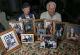 DM0330  Ken and Judy White pose for a portrait with pictures of their family at their home in...