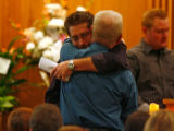 DM6920  Bill Serecky, facing camera, hugs Bob Guntharp during the funeral for Guntharp's wife...