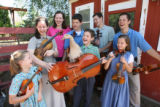 The Johnson siblings pose with their chickens, ducks, and string instruments in the backyard of...