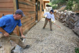 Rex and Heather Heiby rake landscaping rock behind their house that sits on the St. Vrain Creek in...