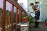 Jennifer Roberts waters her flower pots on her back porch in Denver on Sept. 3, 2008.  It's part...
