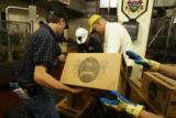 Workers remove a case of new beer during bottling of AC Golden Brewing's fourth batch of Herman...