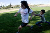 Carlos Covarrubias, 11, (cq) chases his cross country coach Jamie Donaldson, 34 (cq) during a game...