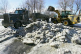 A front-end loader prepares to deposit ice and snow into a dump truck. Private crews, such as this...