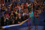 Michelle Obama, and her daughters Sasha (purple dress) and Malia wave to the crowd during the 2008...