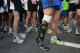 Major Dave Rozelle, in prosthesis, who lost part of his leg in an explosion in Iraq, lines up at...
