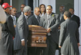 Pallbearers prepare to load the casket into a horsedrawn cason after the funeral for slain...