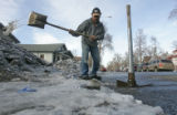 Salvador Venezuela uses a shovel and a pick axe to break up the melting ice in front of his home....