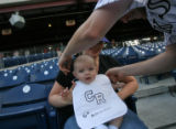Josh Ayers puts a bib on his son Ethan Ayers, 4 months, held by his wife Lindsey Ayers as they...