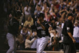 The Colorado Rockies' Seth Smith high-fives Troy Tulowitzki after Smith scored on a sac fly by...