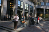 Unidentified commuters wait in lines in front of the Qwest building on their way home. The Qwest...