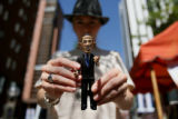 Alyssa Zeller holds a Barack Obama action figure for sale on the 16th Street Mall during the 2008...