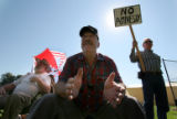 (115)  Jim Haas, left, and Dana Isham, center,  both of Grand Junction listen in to a speach along...