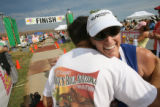 49 year-old Debora Krayna (cq) from Denver, receives a hug after earning a medal for completing...