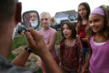 Jeremy Kennis shaves his beard as Cornerstone Dr. neighbors, Ceci Barnhill, 9, Katie Zrubek, 8,...