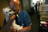 Doctor Tom Ponder embraces a stray dog that was brought to the Windsor Community Recreation Center...