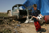 Luke Kennedy, 8, plays with a soccer ball as he helps his cousins and aunt and uncle pick up...