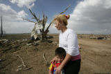 Ilde Dominguez and son Jonathan walk around in the debris looking for salvageable items, including...