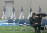 Two members of the crowd sit in the rain before the start of the Air Force Academy graduation...
