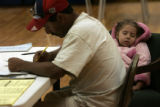 Eduardo Castillo votes while his daughter Yarelin Castillo, 3, sleeps, at the Swansea Recreation...