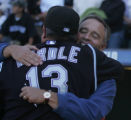 Colorado Rockies general manager Dan O'dowd hugs manager Clint Hurdle after the Rockies defeated...