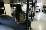 A female inmate sits on her bunk in a work release dorm in Building 21 at the Denver County Jail...